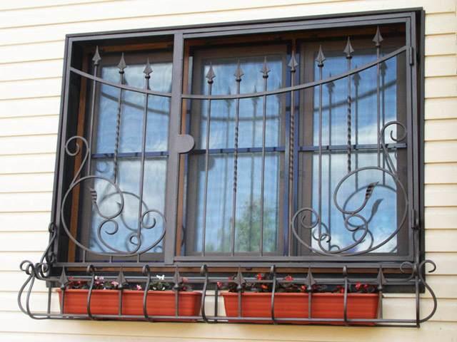 Кованая оконная решетка с пиками и завитками с подставкой под цветы