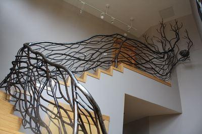 Кованые ветви перил в сочетании с деревянной лестницей