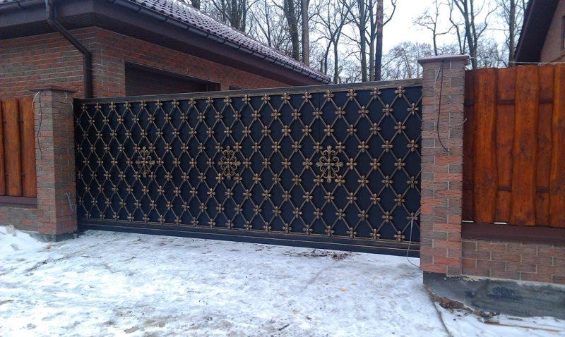 Кованые откатные ворота элегантно дополняют деревянный забор