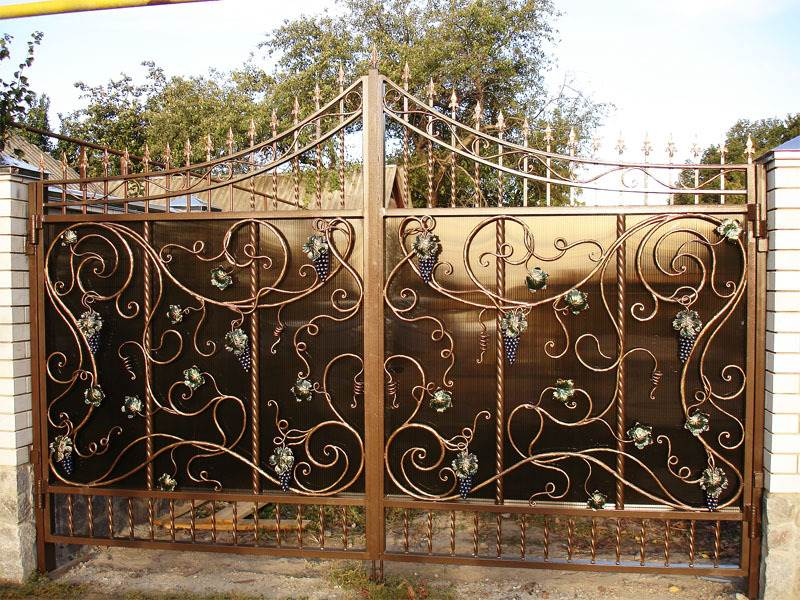 Глухие металлические ворота дополненные коваными гроздьями винограда