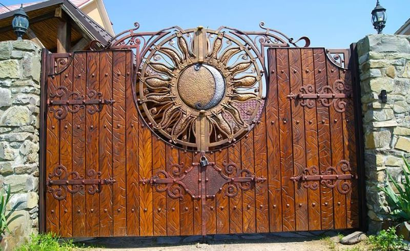 Кованый стиль ворот великолепно сочетается с деревянным полотном