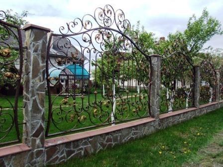 Приятный кованый забор с каменным столбом