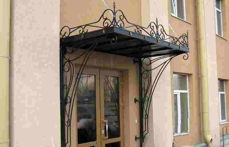 Металлический кованый козырек в оформлении входной двери