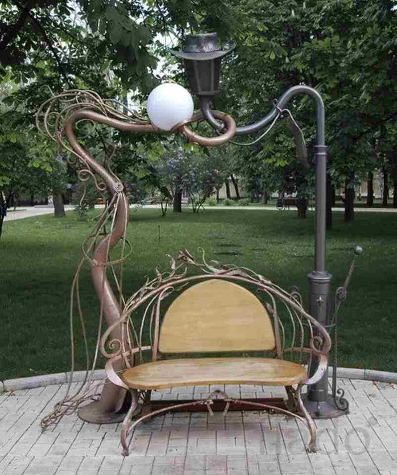 Кованая парковая скамейка и переплетенные фонарные столбы