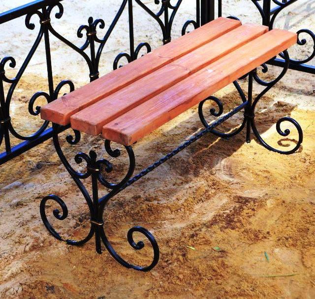 Кованая скамейка на кладбище с деревянной доской
