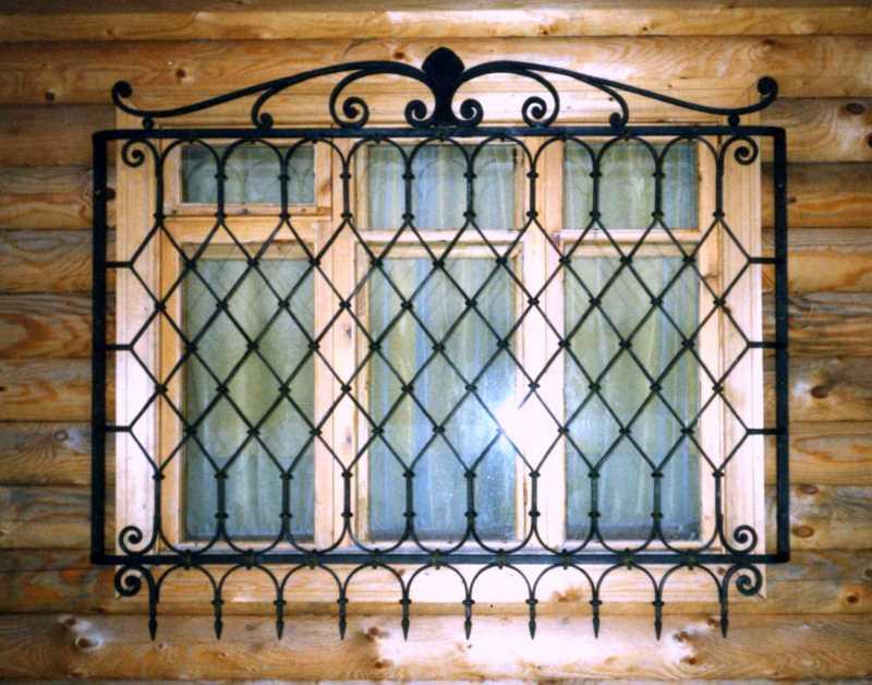 Кованая решетка для окна в деревянном доме