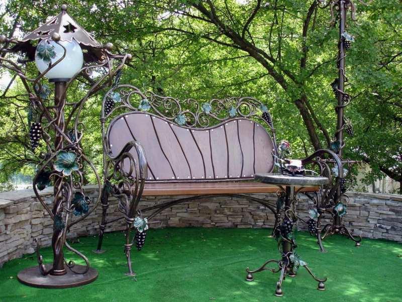 Кованая скамейка со столом и фонарными столбами оплетенные виноградной лозой